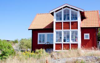 Röd villa på klippa. Blå himmel i bakgrunden