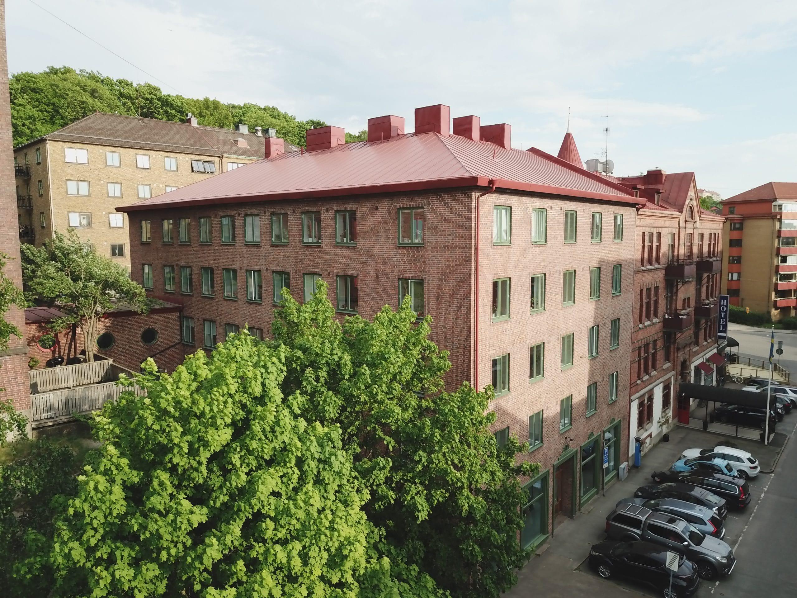 lägenhetshus i brunt tegel med gröna fönster.