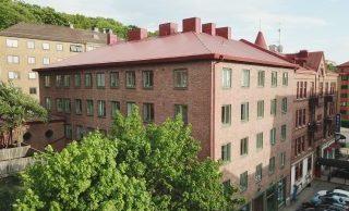 lägenhetshus i brunt tegel med gröna fönster
