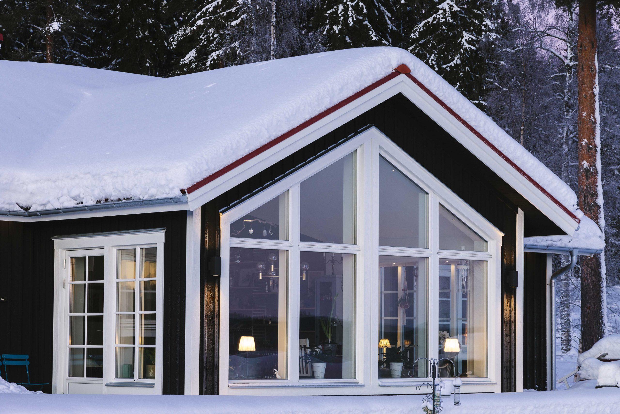 SP-fönster monterade på rött hus med snö