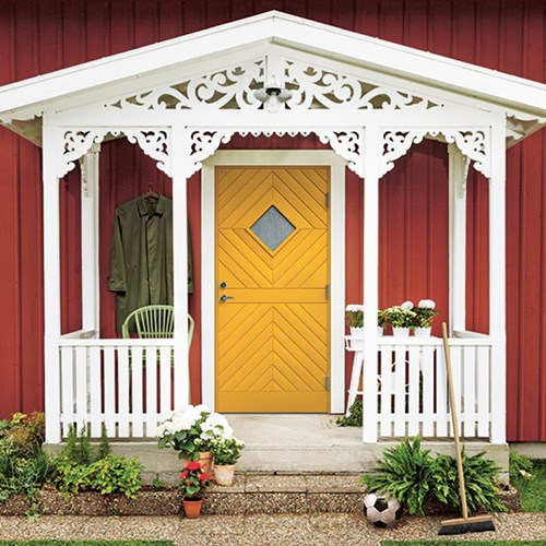 gul ytterdörr med fönster på rött hus